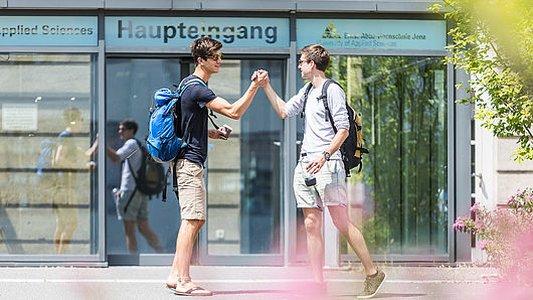 Studierende begrüßen sich vor dem Haupteingang der EAH. - Foto Ernst-Abbe-Hochschule Jena